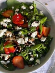 Strawberry Spinach Salad in a white bowl with and fork